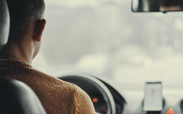 image of man driving a car viewed from back seat